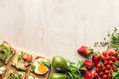 """Постер, картина, фотообои """"вид сверху ингредиентов на деревянный стол и тосты с овощами на разделочная доска"""""""