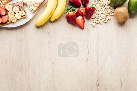 Ansicht von Bananen, Erdbeeren, Erdnüssen und Toasts auf Holztisch mit Kopierraum