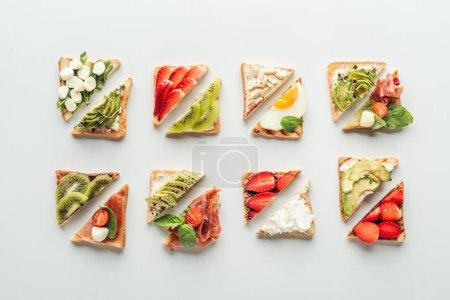 Draufsicht auf köstliche Toastbrot mit Obst und Gemüse isoliert auf weiß