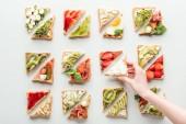 """Постер, картина, фотообои """"обрезанный вид женщина держит кусок хлеба над гренки с фруктами и овощами, изолированные на белом фоне"""""""