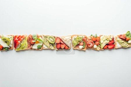 Draufsicht der Toastreihe mit Obst und Gemüse isoliert auf weiß mit Kopierfläche