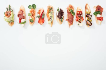 Photo for Top view of traditional italian bruschetta with prosciutto, salmon, fruits, vegetables and herbs on white with copy space - Royalty Free Image