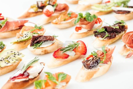 selective focus of italian bruschetta with dried tomatoes, prosciutto, avocado, strawberries and herbs