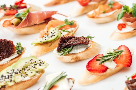 Photo for Selective focus of italian bruschetta with dried tomatoes, prosciutto, avocado, strawberries and herbs on white - Royalty Free Image