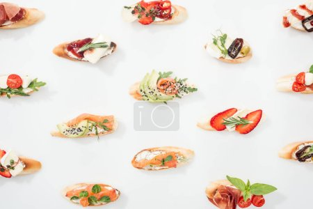 Photo for Background of italian bruschetta with salmon, prosciutto, avocado, strawberries and herbs on white - Royalty Free Image