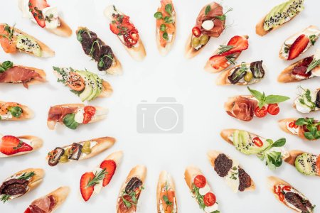 Photo for Top view of round frame made of italian bruschetta with salmon, prosciutto, herbs and various fruits with vegetables on white - Royalty Free Image