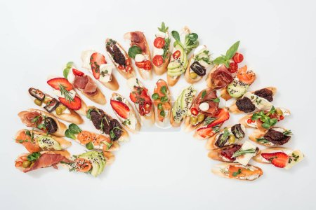 Photo for Top view of traditional italian bruschetta with prosciutto, salmon, fruits, vegetables and herbs on white - Royalty Free Image