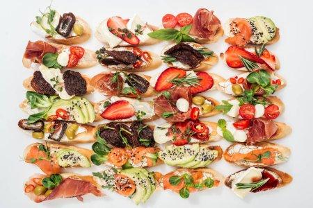 Hintergrund der schmackhaften italienischen Bruschetta mit Lachs, Prosciutto, getrockneten Tomaten, Avocado, Erdbeeren und Kräutern auf weiß