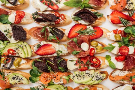 Photo for Background of italian bruschetta with salmon, prosciutto, strawberries, dried tomatoes and herbs isolated on white - Royalty Free Image