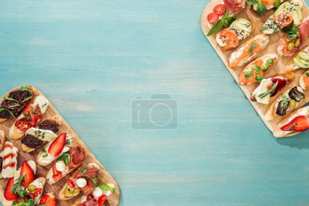 Photo for Top view of italian bruschetta with prosciutto, salmon and herbs on chopping boards with copy space - Royalty Free Image