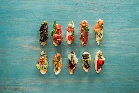 Photo pour Vue de dessus de bruschetta italienne au saumon, tomates séchées, prosciutto et herbes sur table en bois - image libre de droit