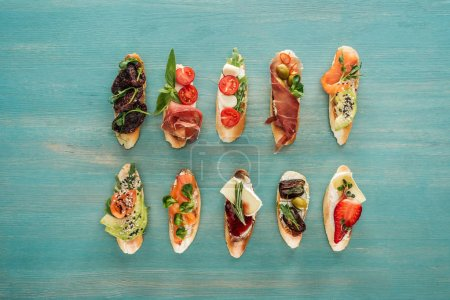 Photo for Top view of italian bruschetta with salmon, dried tomatoes, prosciutto and herbs on wooden table - Royalty Free Image