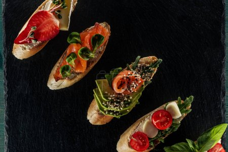 Photo for Top view of italian bruschetta with salmon, tomatoes and avocado on wooden table - Royalty Free Image