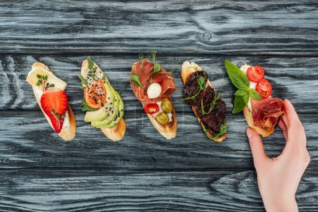 Photo for Cropped view of woman and italian bruschetta with prosciutto, salmon and vegetables on wooden table - Royalty Free Image