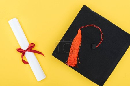 Photo for Top view of academic cap and diploma with red ribbon isolated on yellow - Royalty Free Image