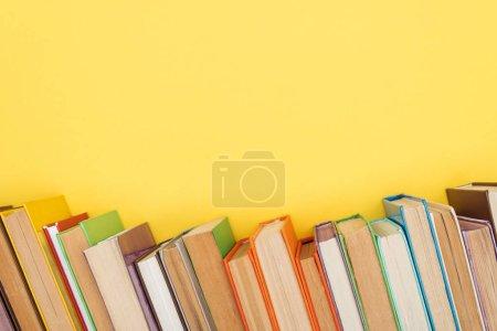 Photo pour Livres colorés lumineux avec des pages sombres isolées sur jaune - image libre de droit
