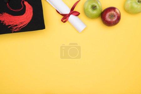 Photo pour Vue de dessus du cap académique, de diplôme et de pommes sur la surface jaune - image libre de droit