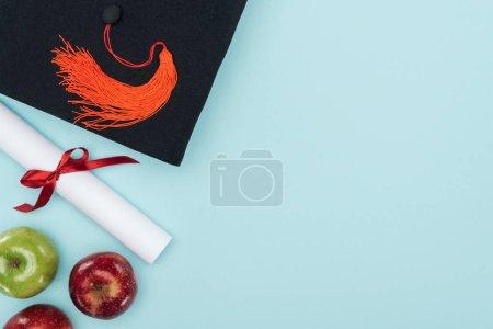 Photo pour Vue de dessus du cap académique, de diplôme et de pommes sur la surface bleue - image libre de droit