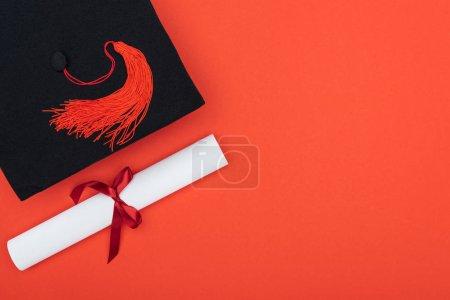 Photo pour Vue de dessus du cap académique et diplôme isolé sur rouge - image libre de droit