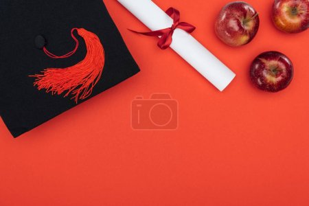 Photo for Top view of academic cap, diploma and apples on red surface - Royalty Free Image