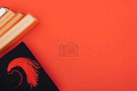Photo pour Vue de dessus des livres et cap académique sur la surface rouge - image libre de droit