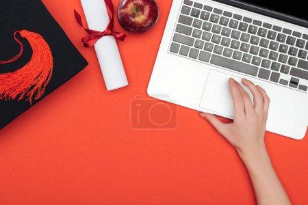 Photo pour Vue recadrée de fille avec cap académique, de diplôme et d'apple à l'aide d'ordinateur portable sur une surface rouge - image libre de droit
