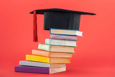 Photo for Academic cap with tassel and bright books on red surface - Royalty Free Image