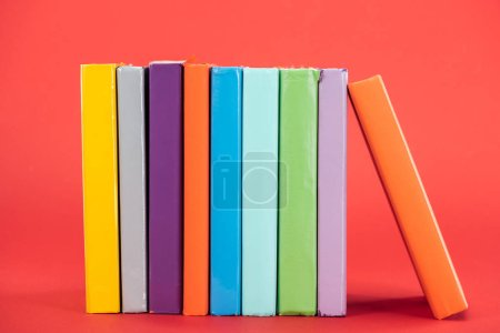 Colorful books with bright hardcovers on red surface