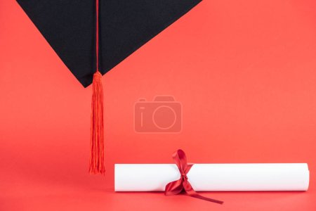 Photo pour Cap académique avec gland et diplôme avec ruban sur la surface rouge - image libre de droit