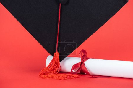 Photo for Academic cap with tassel and diploma with ribbon on red surface - Royalty Free Image