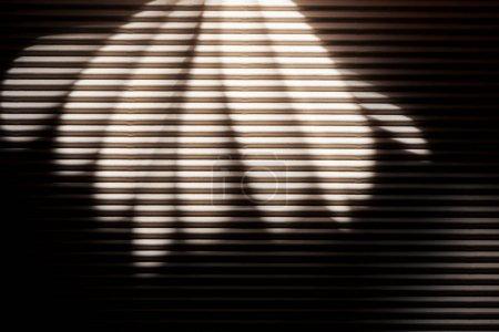 Photo pour Rayons blancs sur surface texturée noire dans l'obscurité - image libre de droit