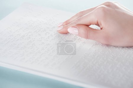 Photo for Close up view of young woman reading braille text on white paper - Royalty Free Image