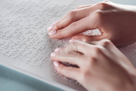 Photo for Cropped view of girl reading braille text with hands on white paper - Royalty Free Image
