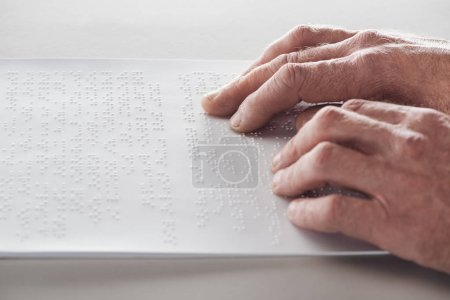 Photo for Cropped view of senior man reading braille text isolated on grey - Royalty Free Image