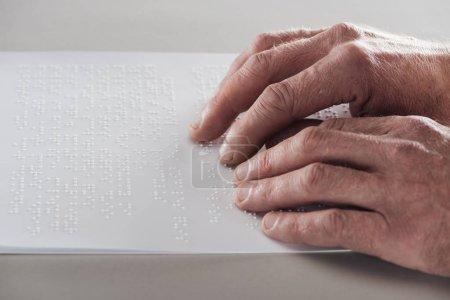 Photo pour Vue partielle de l'homme senior lecture texte braille isolé sur fond gris - image libre de droit