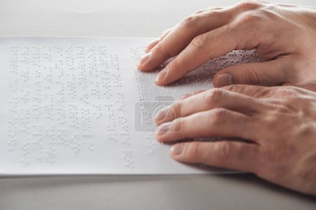 Photo for Cropped view of man reading braille text with hands - Royalty Free Image