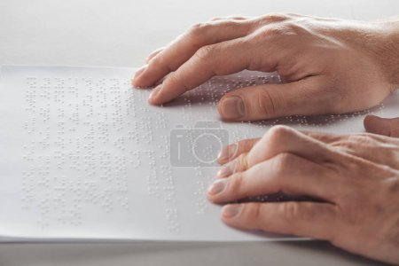 Photo for Cropped view of man reading braille text with hands isolated on grey - Royalty Free Image