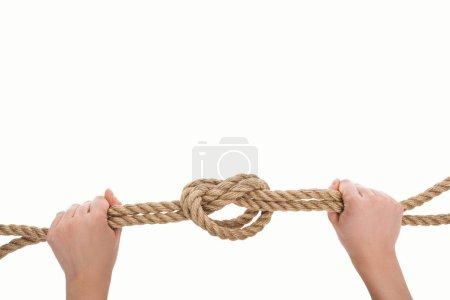 Photo pour Vue recadrée de la femme tenant une corde de jute nautique avec noeud marin isolé sur blanc - image libre de droit