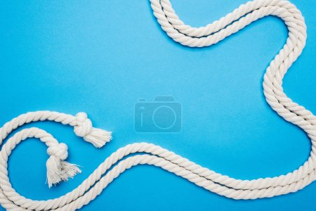 Photo for Long white waved ropes with knots isolated on blue - Royalty Free Image
