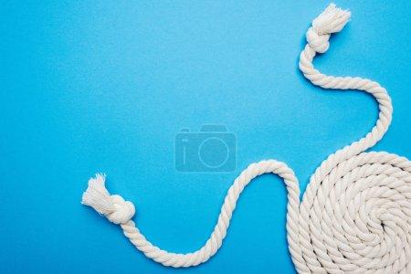 Photo pour Cordes blanches torsadées avec nœuds isolés sur bleu - image libre de droit