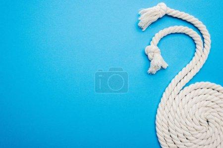 Photo pour Long blanc agité et tordu les cordes avec noeuds isolés sur bleu - image libre de droit