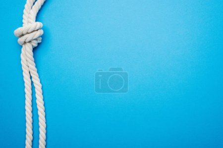 Photo for White long ropes with sea knot isolated on blue - Royalty Free Image