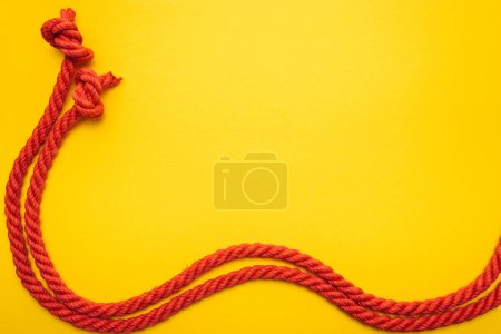 Photo for Red waved ropes with knots isolated on orange - Royalty Free Image