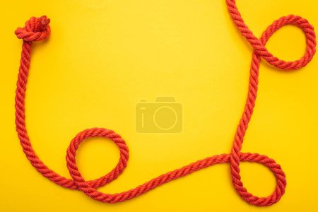 Photo for Curled and red rope with twisted knot isolated on orange - Royalty Free Image
