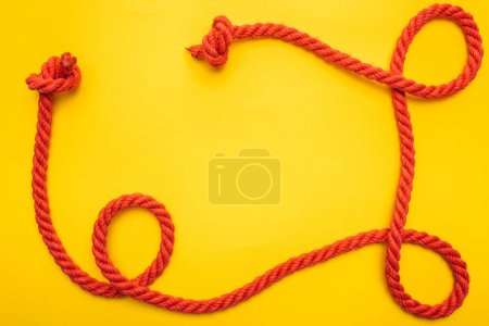 Photo for Curled and red rope with twisted knots isolated on orange - Royalty Free Image