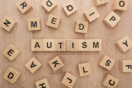 Photo for Top view of autism lettering made of wooden cubes with different letters on wooden table - Royalty Free Image