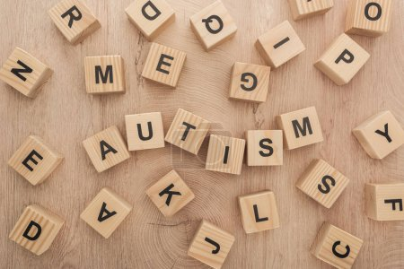 Photo for Top view of autism lettering made of wooden cubes with different letters on table - Royalty Free Image