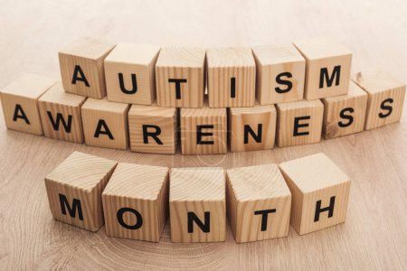 Photo for Autism awareness month words made of wooden cubes - Royalty Free Image