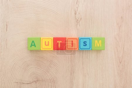 Photo for Top view of autism lettering made of multicolored cubes on wooden table - Royalty Free Image