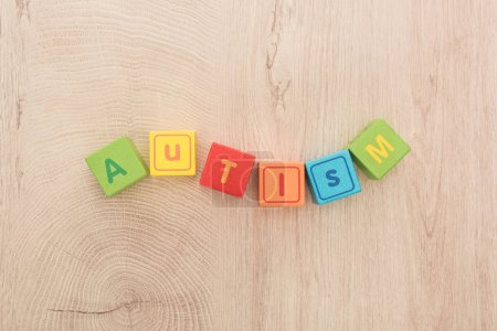 Photo for Top view of wavy autism lettering made of multicolored cubes on wooden table - Royalty Free Image